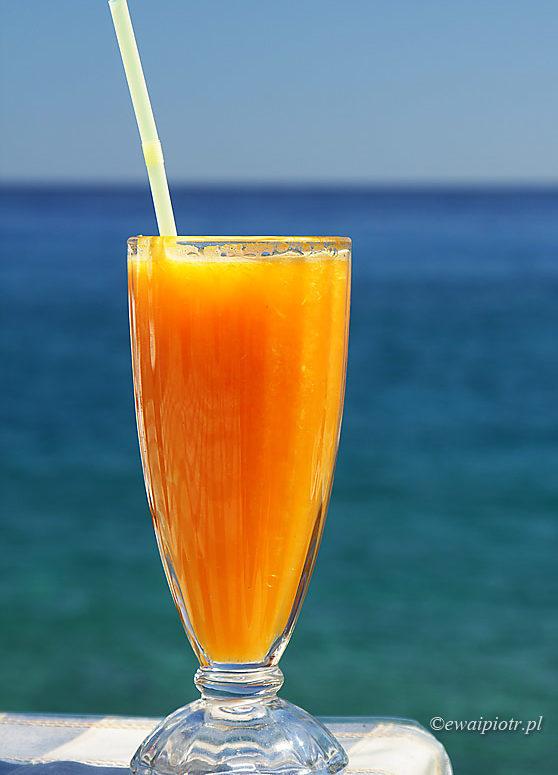 Sok pomarańczowy i morze, Kreta, szklanka soku na tle morza