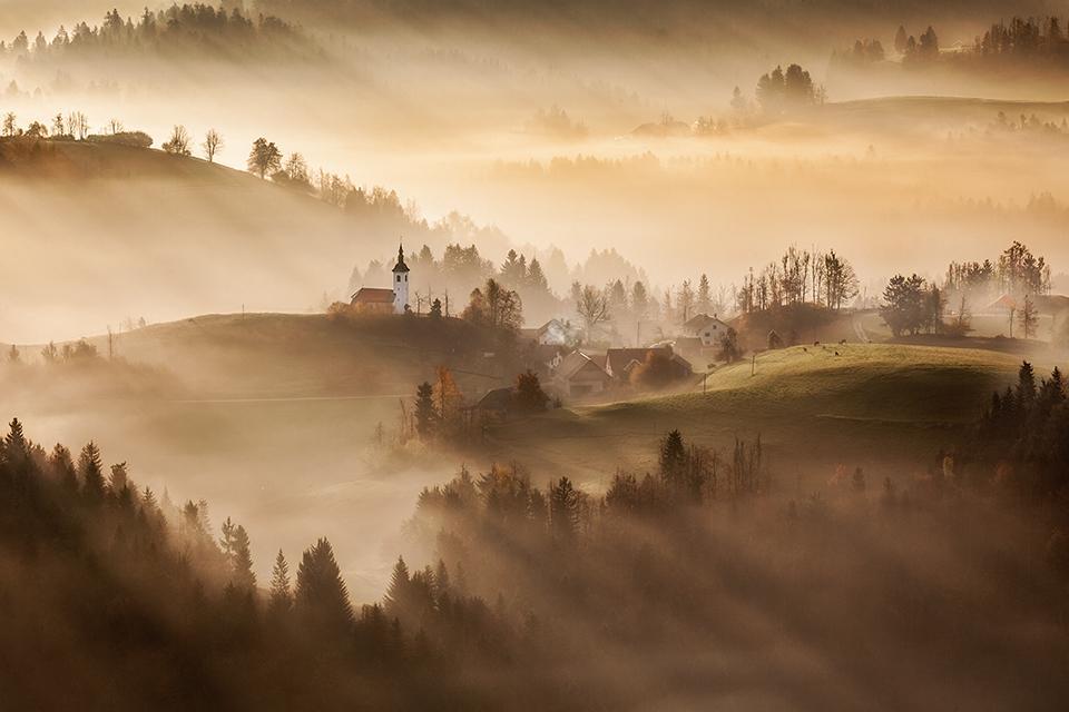 Wzgórza o wschodzie, smugi światła, mgła, fotowyprawa do Słowenii