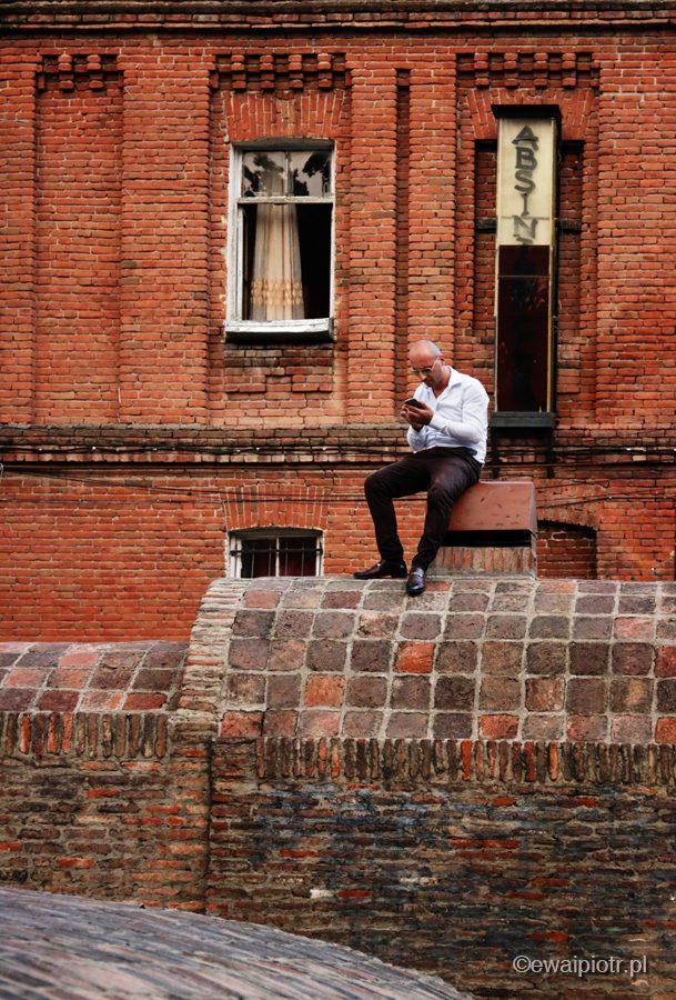 Mężczyzna ze smartfonem, łaźnie w Tbilisi, warsztaty fotograficzne Gruzja