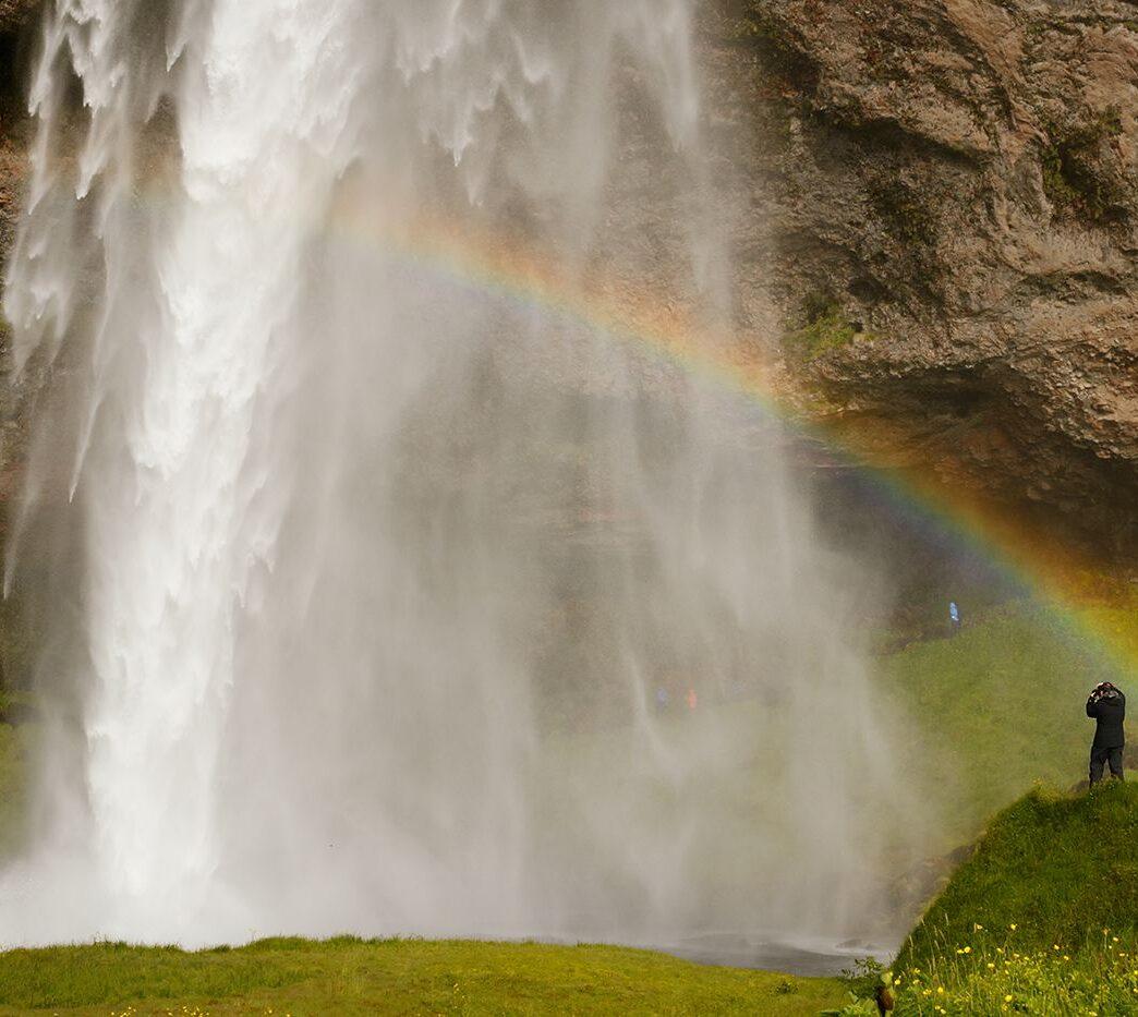 Człowiek, wodospad i tęcza, Seljalandsfoss, Islandia
